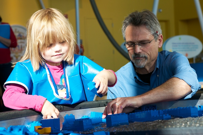 Early interest in science is a good predictor of a career in the field. Here, EDC's Jeff Winokur helps a student use Legos to change the flow of water.