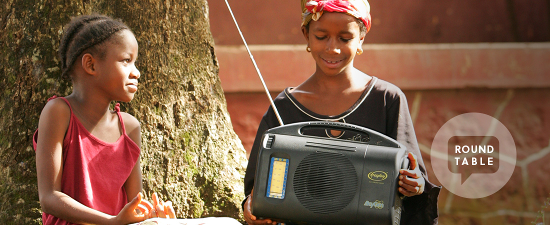 A photo of a teacher and student using a radio