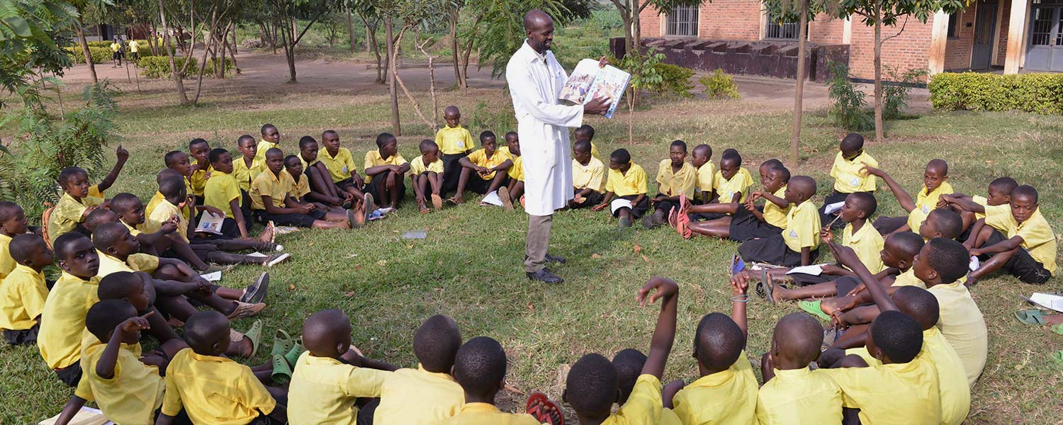 A teacher reads to students in Rwanda.