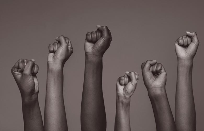 A photo of raised hands representing Lift Every Voice