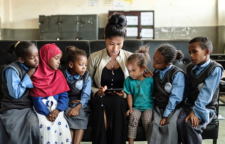 A photo of teacher and students reading representing Celebrating the Importance of Books
