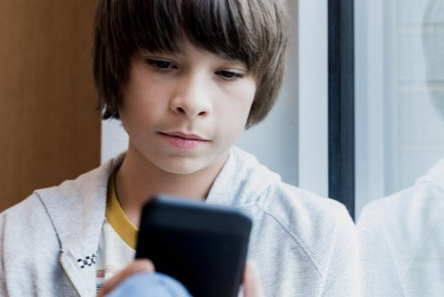 A teen using a phone representing Fighting Misinformation through Media Literacy