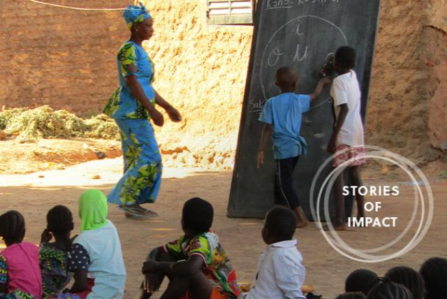 A photo of students and teacher representing Reading Inspires Students, Parents in Mali
