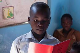 A child in Zambia works in his reading skills.