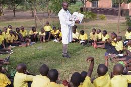 A teacher reads to students in Rwanda.